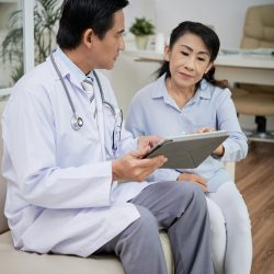 General practitioner explaining senior woman how to use healthcare application on tablet computer on tablet computer